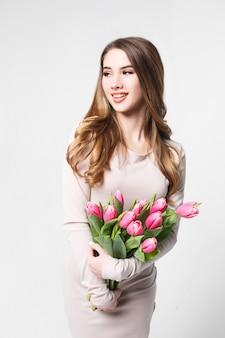 Bela jovem loira com um buquê de tulipas cor de rosa isoladas na parede branca.