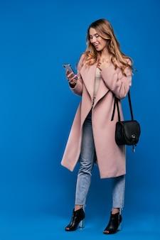 Bela jovem loira com uma capa de chuva em uma parede azul com telefone celular