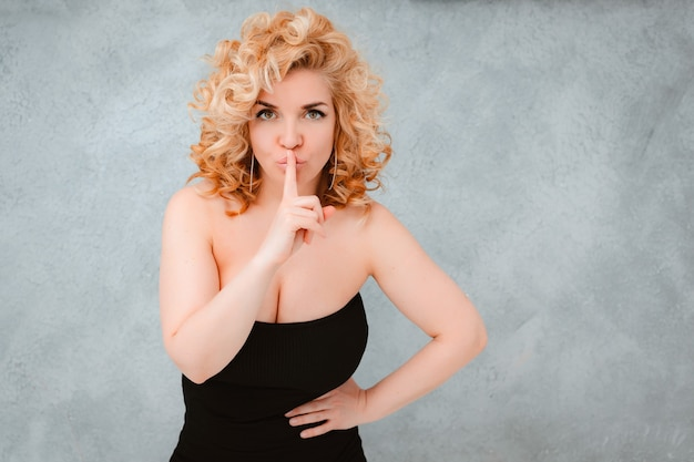 Bela jovem loira de cabelos cacheados com o dedo nos lábios