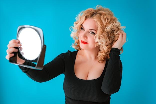 Bela jovem loira de cabelos cacheados em um vestido preto segurando um espelho