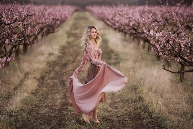 Bela jovem loira de cabelos cacheados em uma saia pregueada marrom, blusa rosa, ombros cobertos com um xale, em pé em jardins de pêssegos