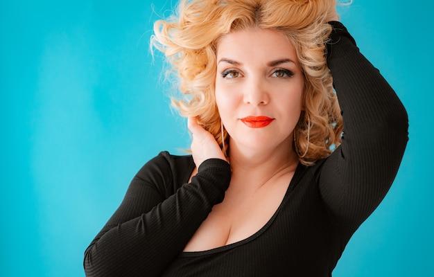 Bela jovem loira de cabelos cacheados posando de vestido preto