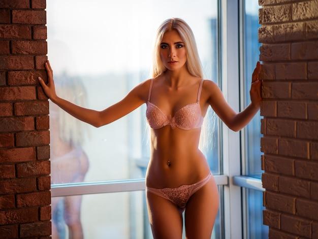 Bela jovem loira de cabelos compridos em roupa íntima elegante, posando no contexto de uma grande janela entre duas paredes de tijolo