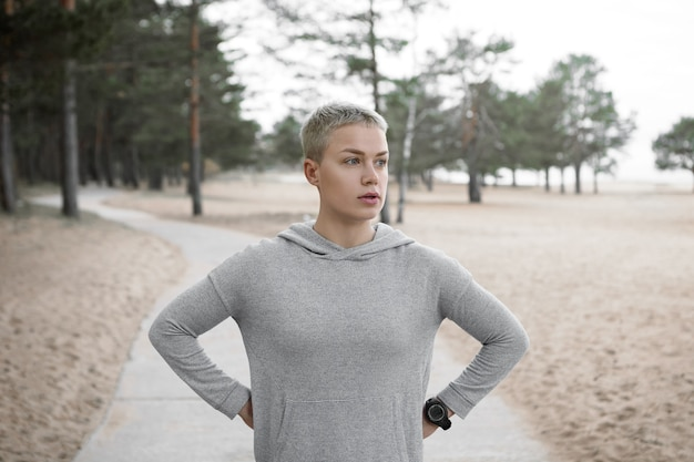 Bela jovem loira de cabelos curtos desportiva com aparência cansada, recuperando o fôlego após a corrida matinal, segurando as mãos na cintura dela, posando em uma trilha pavimentada contra uma praia de areia e pinheiros ao fundo