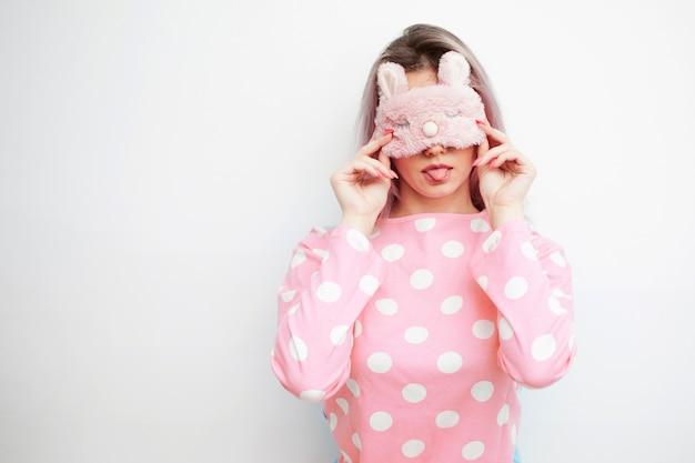Bela jovem loira de pijama rosa e uma máscara de dormir nos olhos