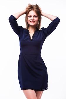 Bela jovem loira de vestido preto em pé sobre um fundo cinza