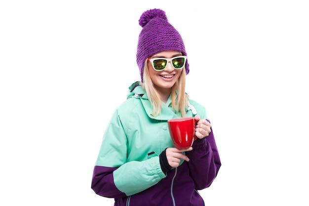Bela jovem loira em traje de neve colorido segurar copo vermelho