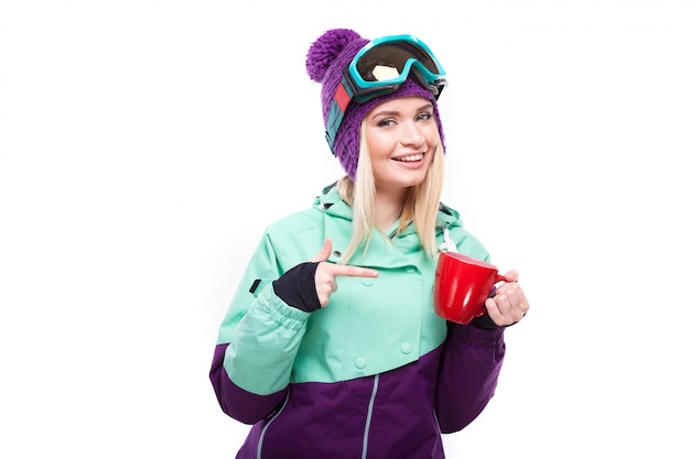 Bela jovem loira em traje de neve colorido segurar o copo vermelho