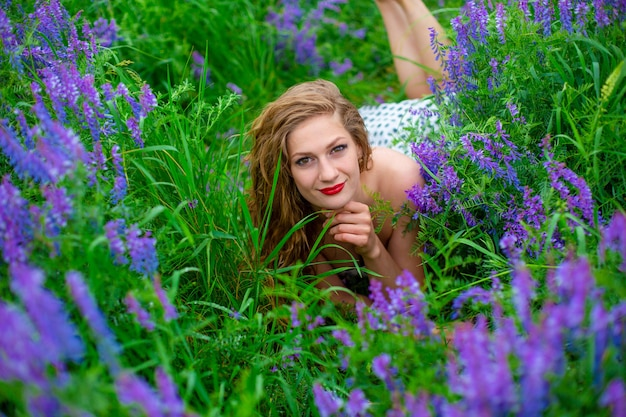 Bela jovem loira em um campo verde entre flores silvestres roxas. garota linda de vida selvagem.