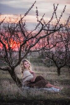 Bela jovem loira encaracolada com saia plissada marrom, blusa rosa, ombros cobertos com lenço de malha, sentada em jardins de flores de pêssego
