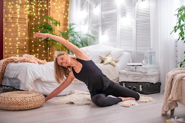 Bela jovem loira, esticando os músculos dos braços e costas, realiza exercícios de ginástica em casa. com espaço de texto livre