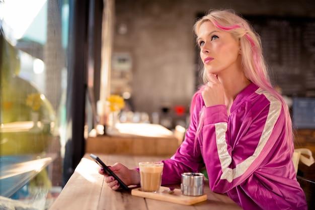 Bela jovem loira pensando enquanto usa o telefone na cafeteria