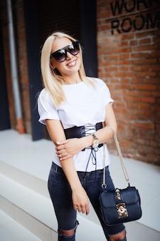 Bela jovem loira posando perto de uma parede de tijolos e sorrindo