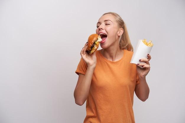 Bela jovem loira positiva com penteado de rabo de cavalo, mantendo os olhos fechados enquanto saboreia seu saboroso hambúrguer, em pé sobre um fundo branco em roupas casuais