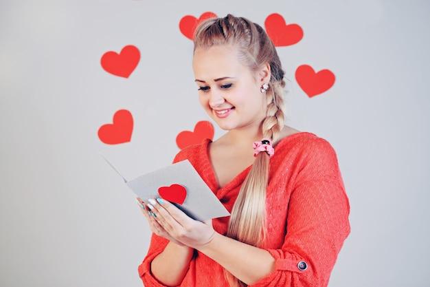 Bela jovem loira segurando um cartão com o coração