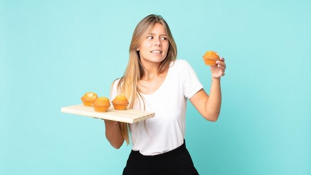 Bela jovem loira segurando uma bandeja de muffins