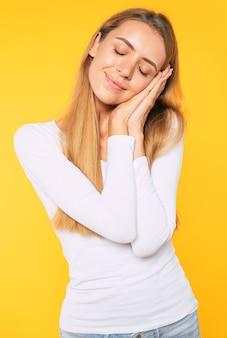 Bela jovem loira sobre fundo amarelo isolado dormindo cansada, sonhando e posando com as mãos juntas