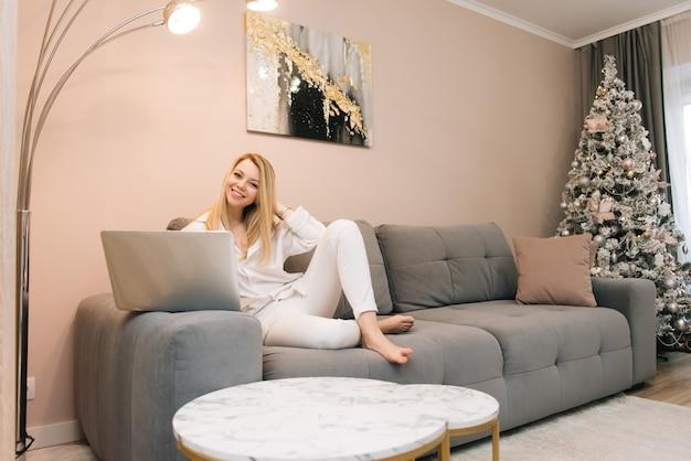 Bela jovem loira sorridente com laptop em casa no sofá, trabalho remoto de casa, isolamento