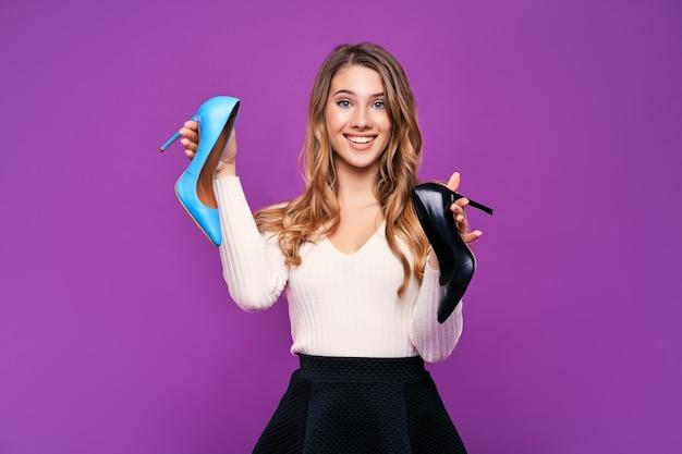 Bela jovem loira sorridente segurando sapatos em uma parede rosa