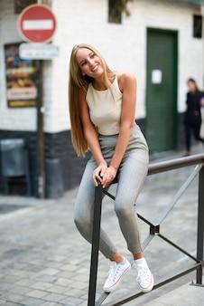 Bela jovem loira sorrindo em um fundo urbano.