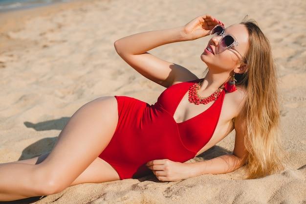 Bela jovem loira tomando banho de sol na praia de areia em um maiô vermelho, óculos de sol