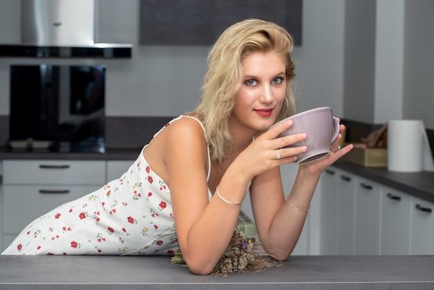 Bela jovem loira tomando café na cozinha