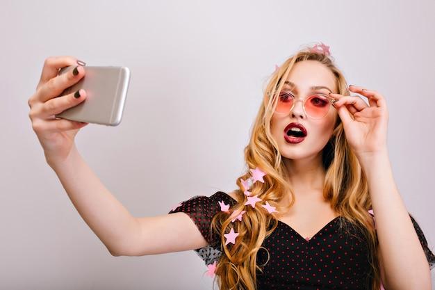 Bela jovem loira tomando selfie na festa, fazendo um look sexy com a boca aberta. usando óculos cor-de-rosa elegantes, vestido preto, tem lindos cabelos cacheados e longos.