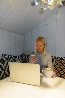 Bela jovem loira usando telefone celular com xícara de café e laptop em casa