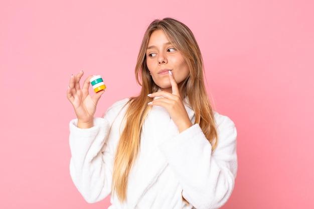Bela jovem loira vestindo roupão de banho e segurando um produto cosmético