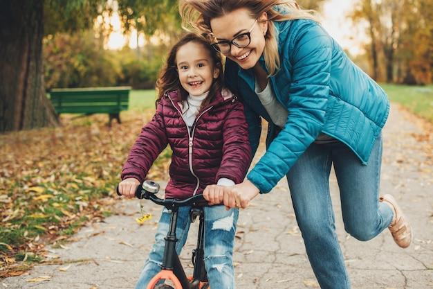 Bela jovem mãe ajudando a filha a aprender a andar de bicicleta no parque. menina bonitinha aprendendo a andar de bicicleta com a mãe.