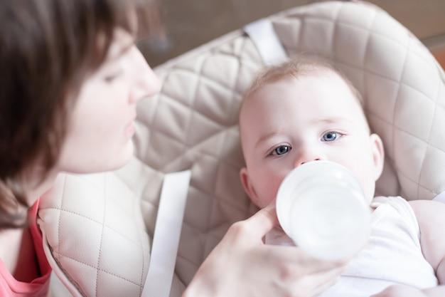 Bela jovem mãe alimentando seu bebê da garrafa
