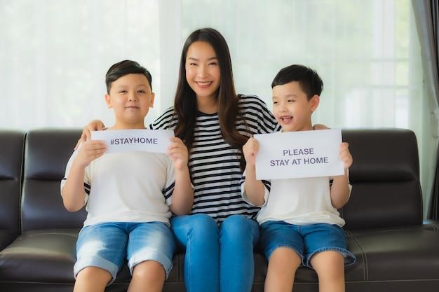 Bela jovem mãe asiática com seus dois filhos mostra papel para ficar em casa para proteger o coronavírus
