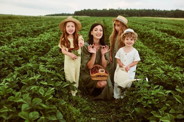 Bela jovem mãe com filhos em um vestido de linho com uma cesta de morangos reúne uma nova safra e se diverte com as crianças
