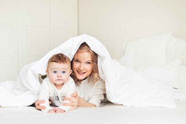Bela jovem mãe com seu filho na cama. manhã engraçada e sorridente. quarto branco