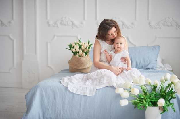 Bela jovem mãe com um bebê nos braços está de pé