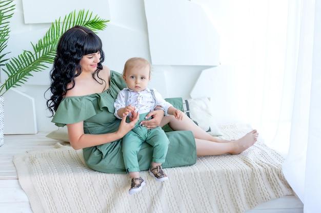 Bela jovem mãe com um bebê nos braços, sentado em uma sala iluminada com roupas verdes, mãe e filho