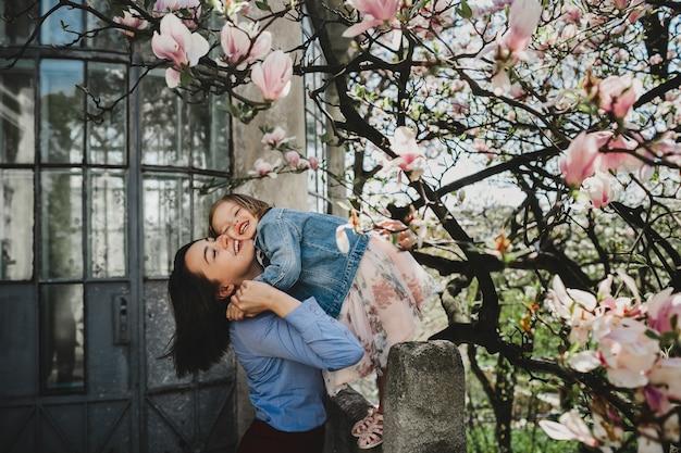 Bela jovem mãe detém linda filhinha em pé debaixo da floração rosa árvore