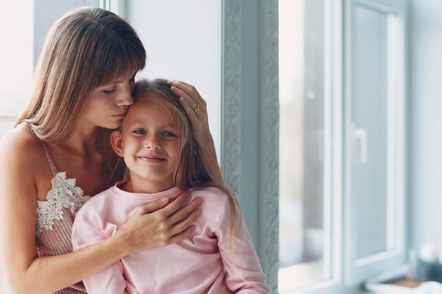 Bela jovem mãe e sua filha encantadora estão abraçando e sorrindo perto da janela do dia.