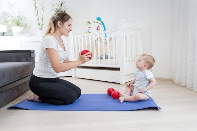 Bela jovem mãe fazendo exercícios e dando halteres para seu bebê. conceito de esporte familiar