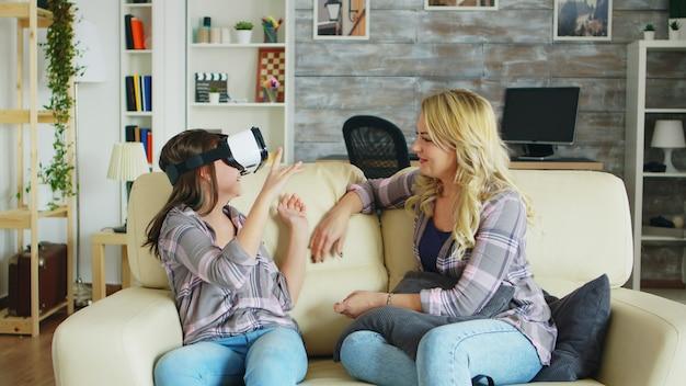 Bela jovem mãe sentada no sofá, olhando para sua filha alegre usando fone de ouvido de realidade virtual.