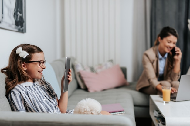 Bela jovem mãe trabalhando em casa enquanto sua filha assistia a aula da escola online. distanciamento social e estilo de vida covid-19 ou coronavirus.