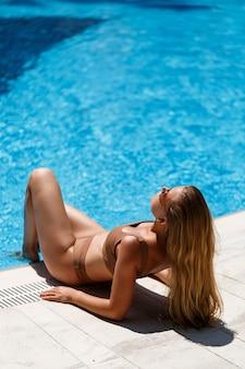 Bela jovem magra com longos cabelos loiros em um maiô bege, descansando perto da piscina com água azul