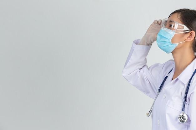 Bela jovem médico está usando máscara enquanto tocar em seus óculos com luvas de borracha na parede cinza.