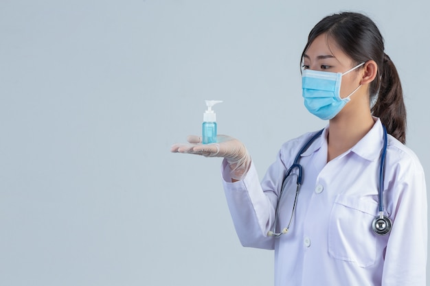 Bela jovem médico está usando máscara, mantendo as mãos gel na parede cinza.