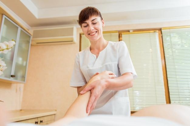 Bela jovem médico massagista em um salão de beleza, fazendo massagem na mão uma menina grávida com cabelos longos