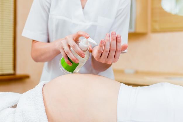 Bela jovem médico massagista em um salão de beleza, lubrificando a barriga de uma paciente grávida (fechar)