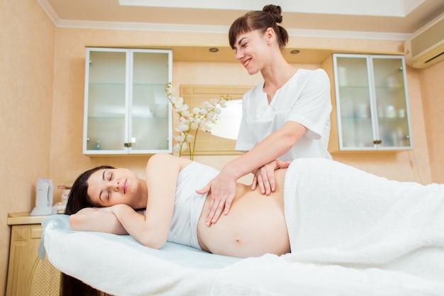 Bela jovem médico massagista em uma sala de cosmetologia, fazendo uma massagem para uma garota grávida com cabelos longos