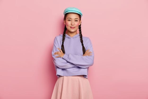 Bela jovem modelo com expressão satisfeita, mantém os braços cruzados sobre o peito, olha positivamente para a câmera, usa boné, blusão e saia elegantes, tem duas tranças, isolada sobre a parede rosa do estúdio