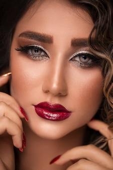 Bela jovem modelo com lábios vermelhos e manicure francesa.