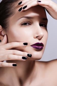Bela jovem modelo com maquiagem brilhante e manicure